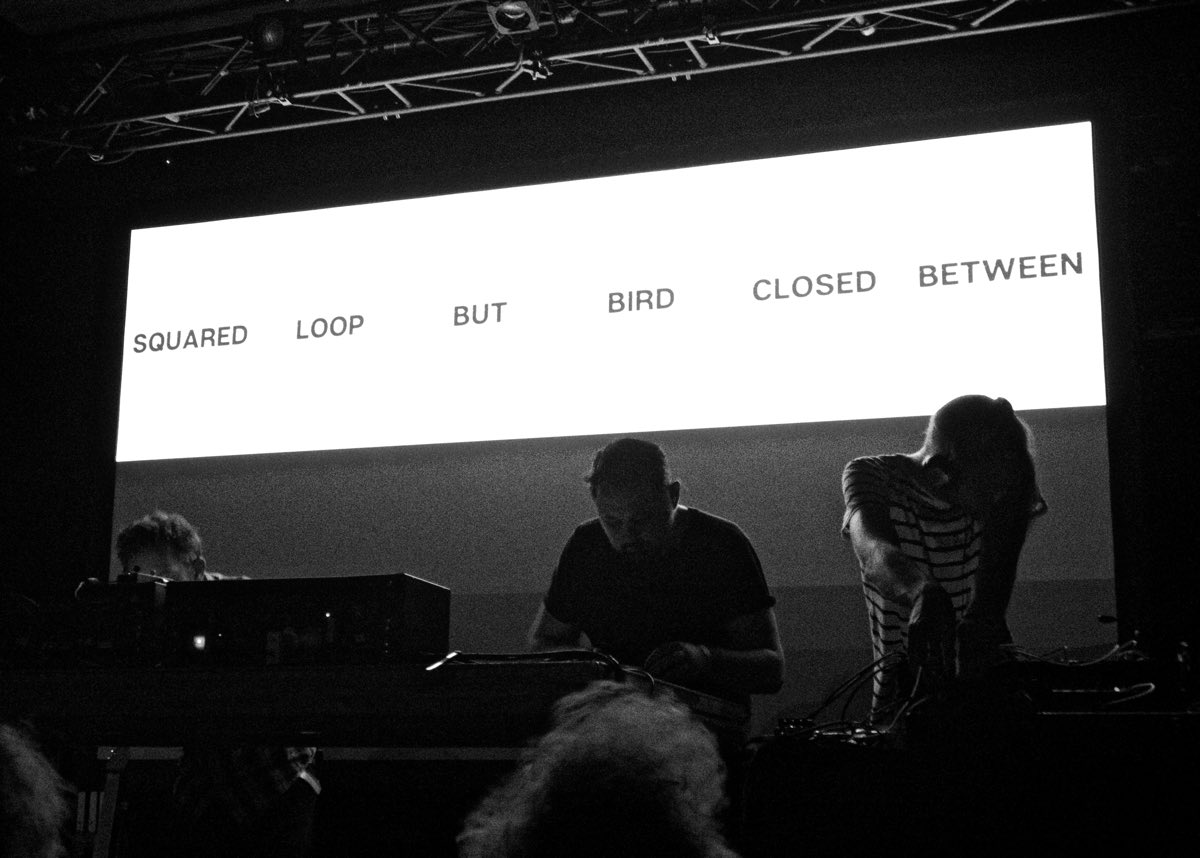 Black and white photo of 65daysofstatic performing their Decomposition Theory piece