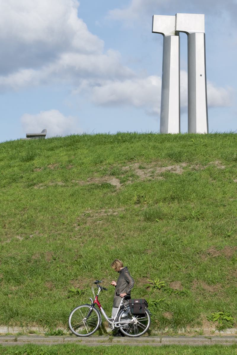 Woman standing by her bike checking her phone, in front of a hill with top of it the artwork Ver-kijkers by Bertie Kiewiet