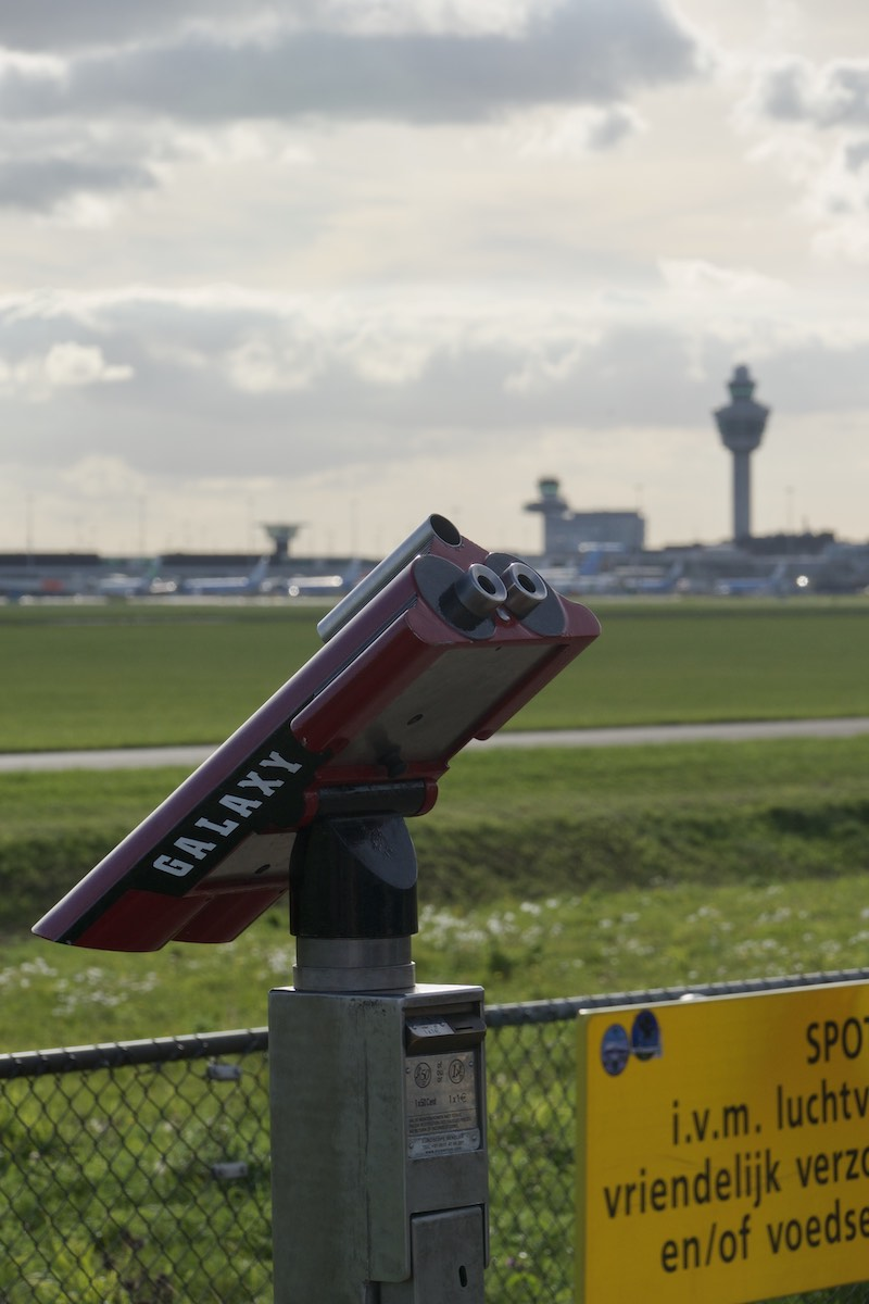 Binoculars for plane spotting, with Schiphol air control tower in the background