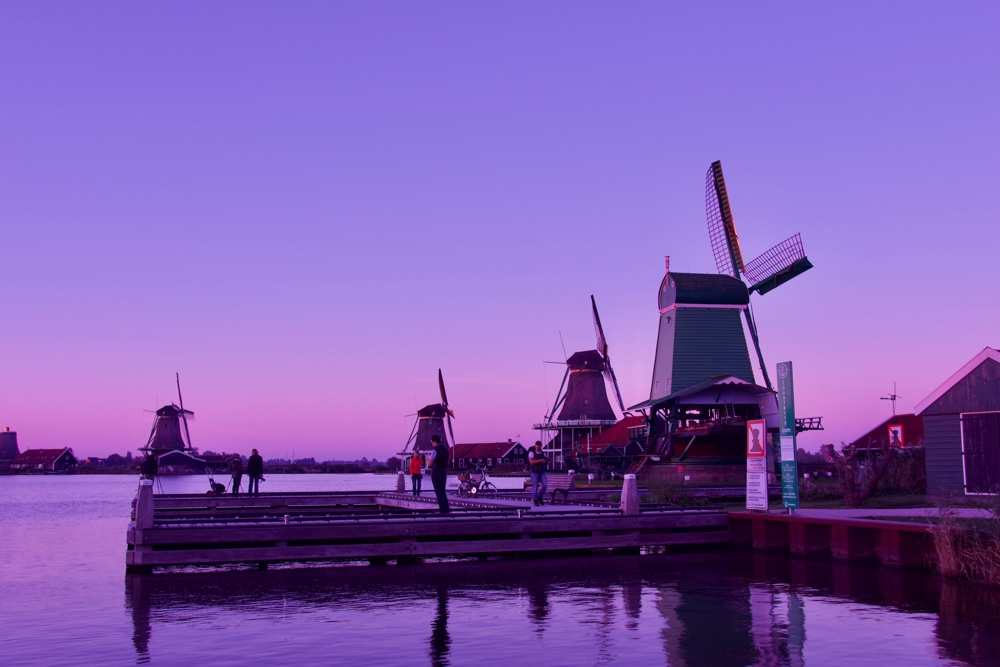 Zaan river at Zaanse Schans. Windmills in the background, and people on a jetty in the foreground.