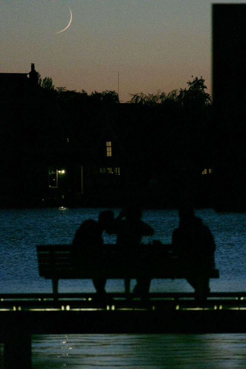 Zaan rover at near-dark. Setting crescent moon in the background across the river. Three people silhouetted on a bench in the foreground.