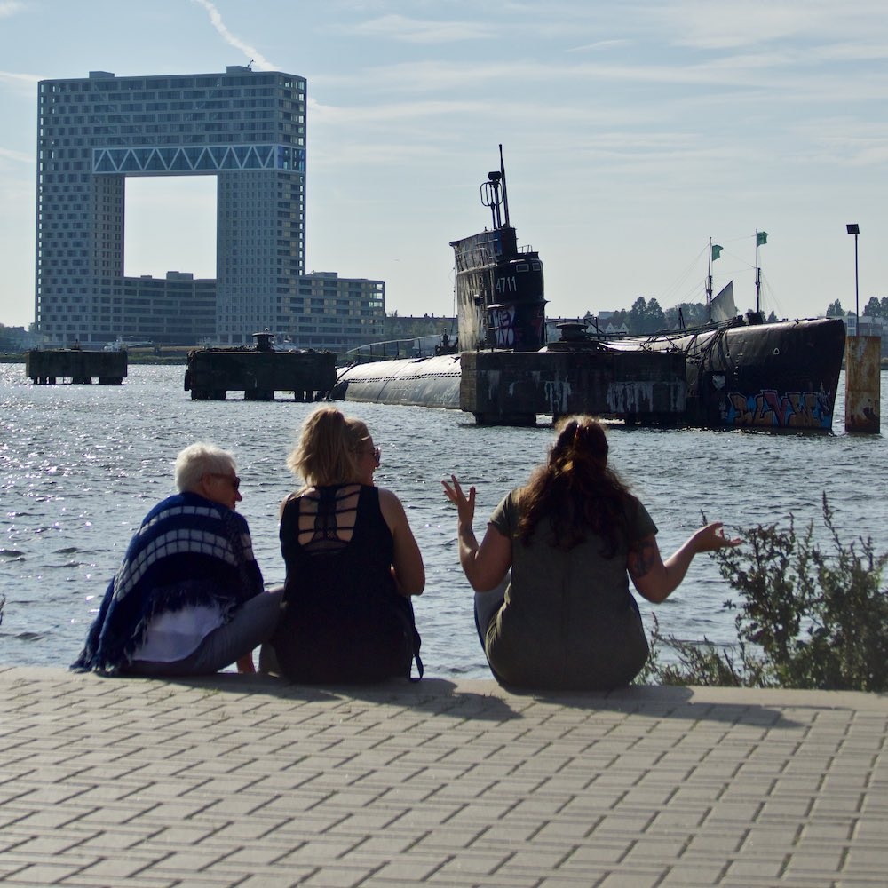 Three people sitting on the edge of the NDSM pier, with a submarine in the water in the background