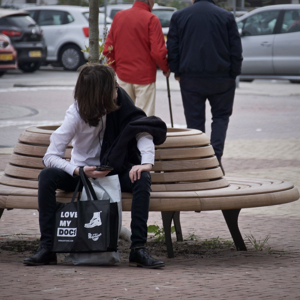 Alex Sutherland sitting on a bench and looking around