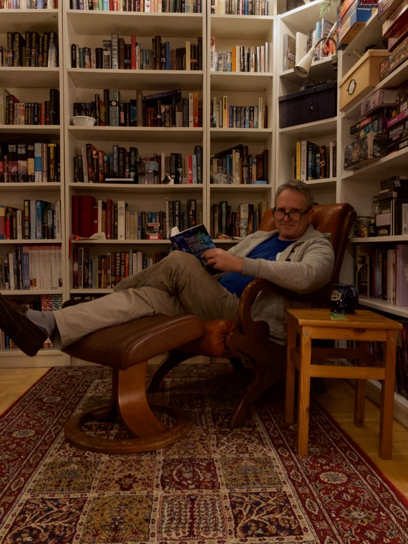 Martin Sutherland relaxing in his reading chair with the new Charles Stross book The Labyrinth Index