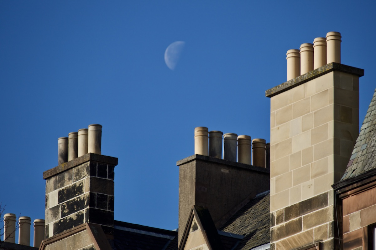 Half moon hanging in the sky above some chimneys